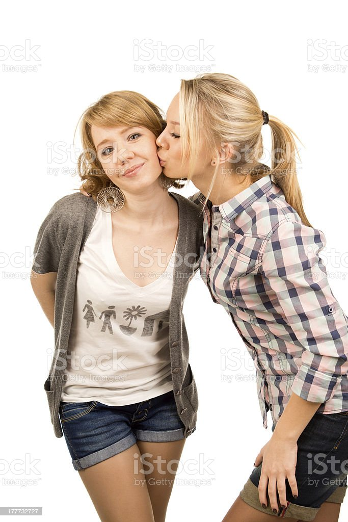 Affectionate teenager giving her friend a kiss royalty-free stock photo