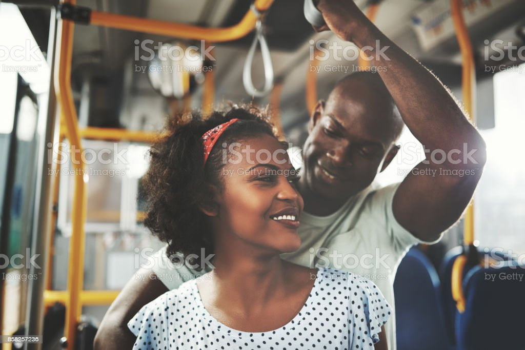 Affectionate young African couple riding together on a bus stock photo