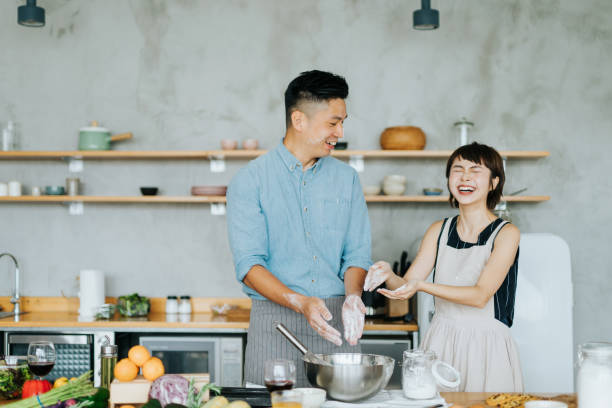 Affectionate young Asian couple having fun while baking together in a domestic kitchen Affectionate young Asian couple having fun while baking together in a domestic kitchen baking bread stock pictures, royalty-free photos & images