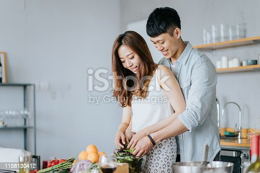 Affectionate young couple cooking together in the kitchen, they are mixing salad with hands