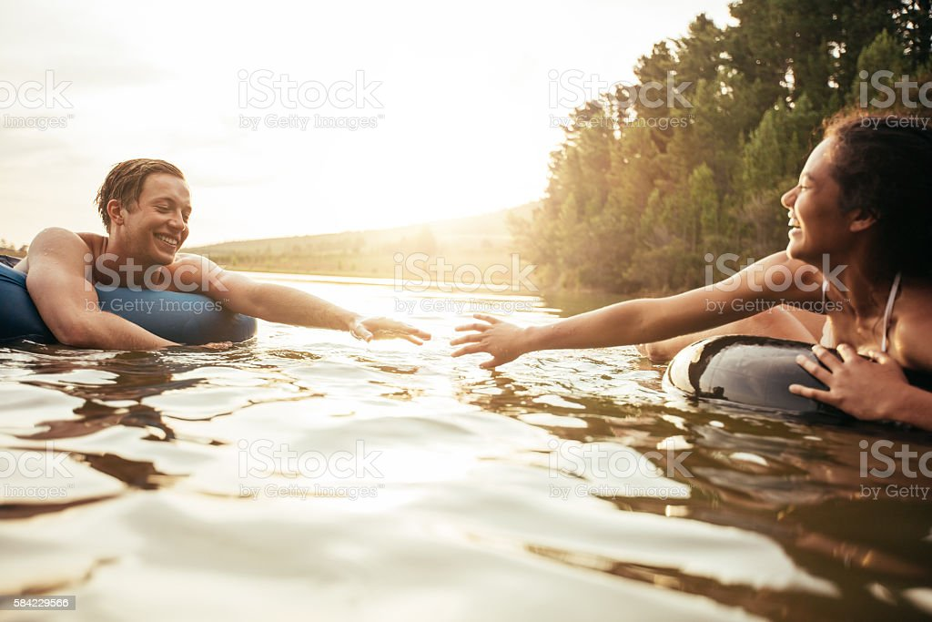 Affectionate young couple floating on inner tubes in lake stock photo
