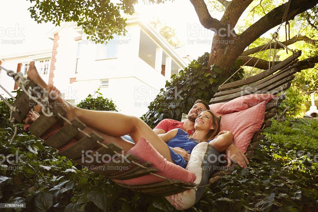 Affectionate young couple lying on garden hammock stock photo