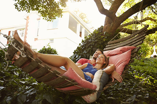 affectionate young couple lying on garden hammock - hangmat stockfoto's en -beelden