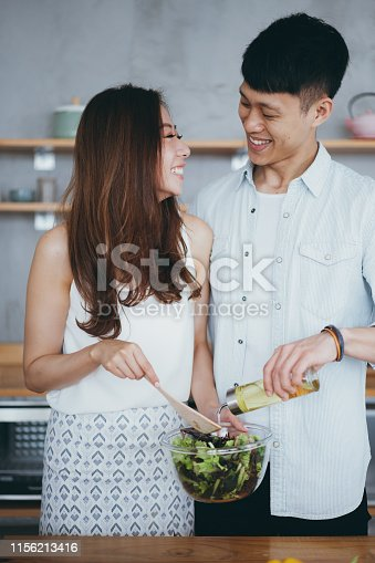 Affectionate young couple preparing salad in kitchen together