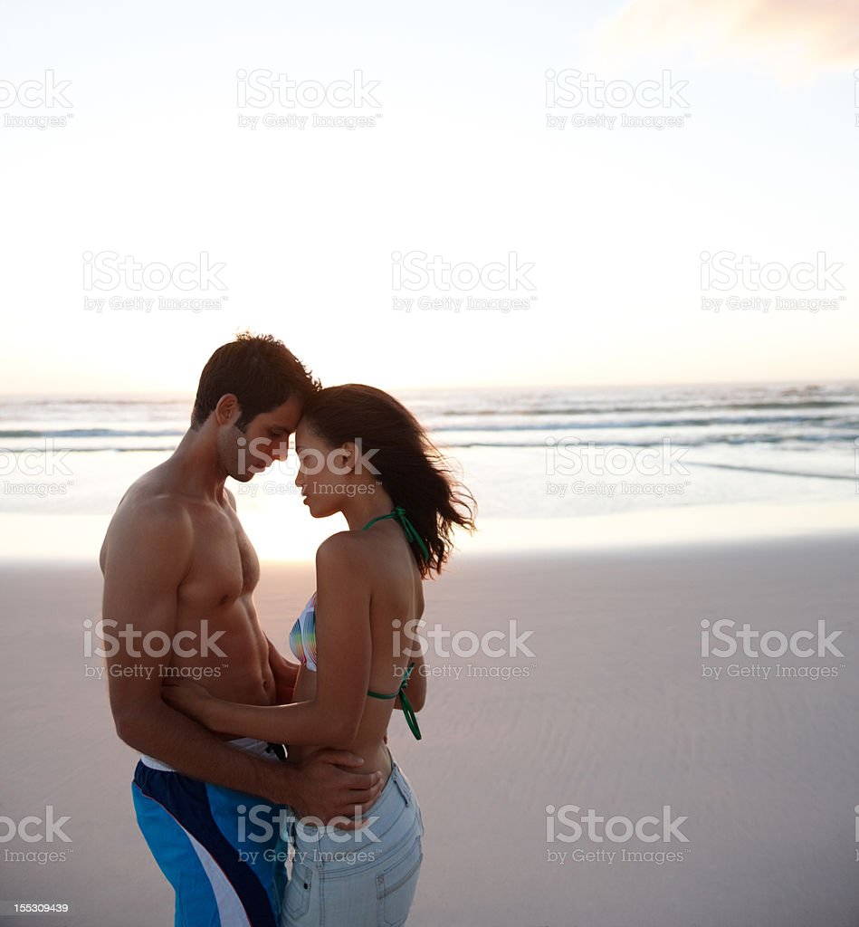 Affectionate young couple romancing at the beach royalty-free stock photo