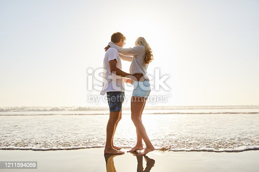 Affectionate young couple standing arm in arm together on a sandy beach looking out at the horizon