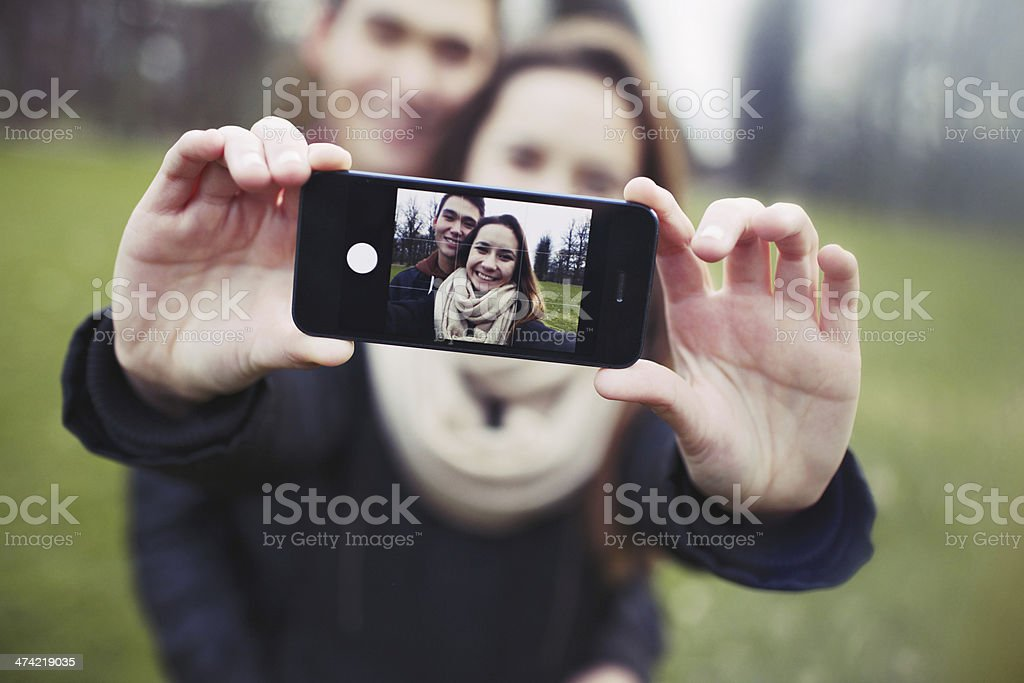 Affectionate young couple taking a self-portrait with smartphone stock photo