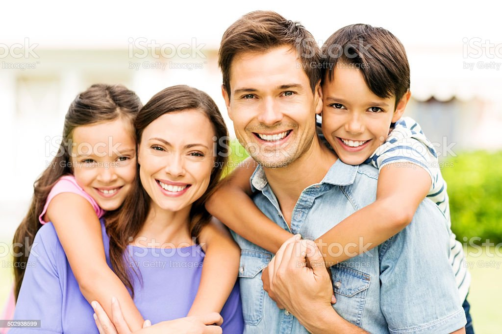 Affectionate Young Family Giving Piggyback Ride stock photo