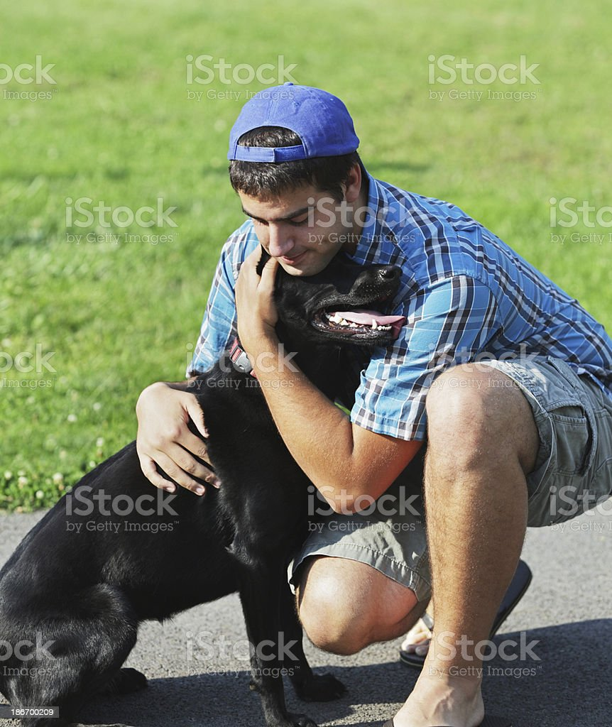 Affectionate Young Man Hugging Black Labrador Retriever royalty-free stock photo