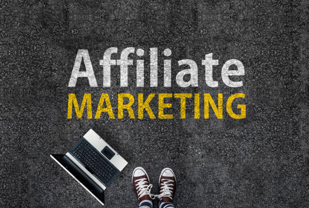 Affiliate marketing man in shoes standing on asphalt next to laptop and affiliate marketing words affiliate stock pictures, royalty-free photos & images