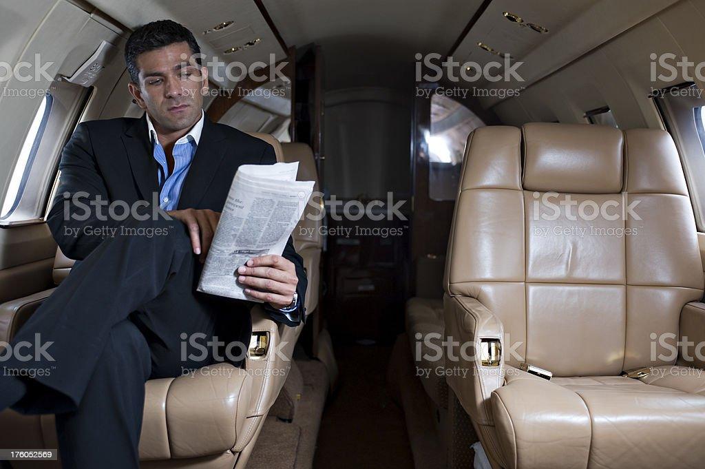 Affluent Travel - Businessman reading newspaper in corprate jet royalty-free stock photo