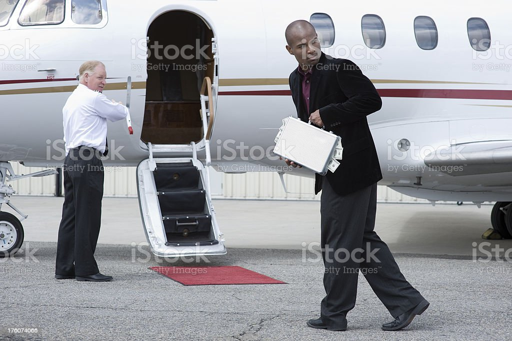 Affluent Travel - Man boarding jet with briefcase and cash royalty-free stock photo