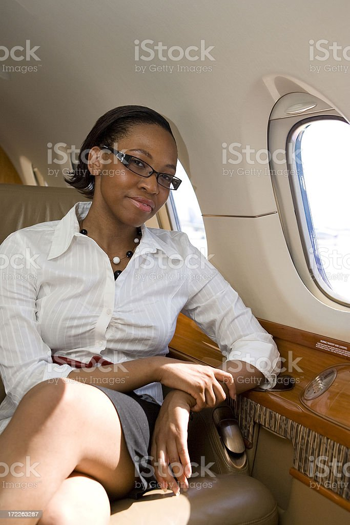 Affluent Travel-African American Female Inside Airplane stock photo