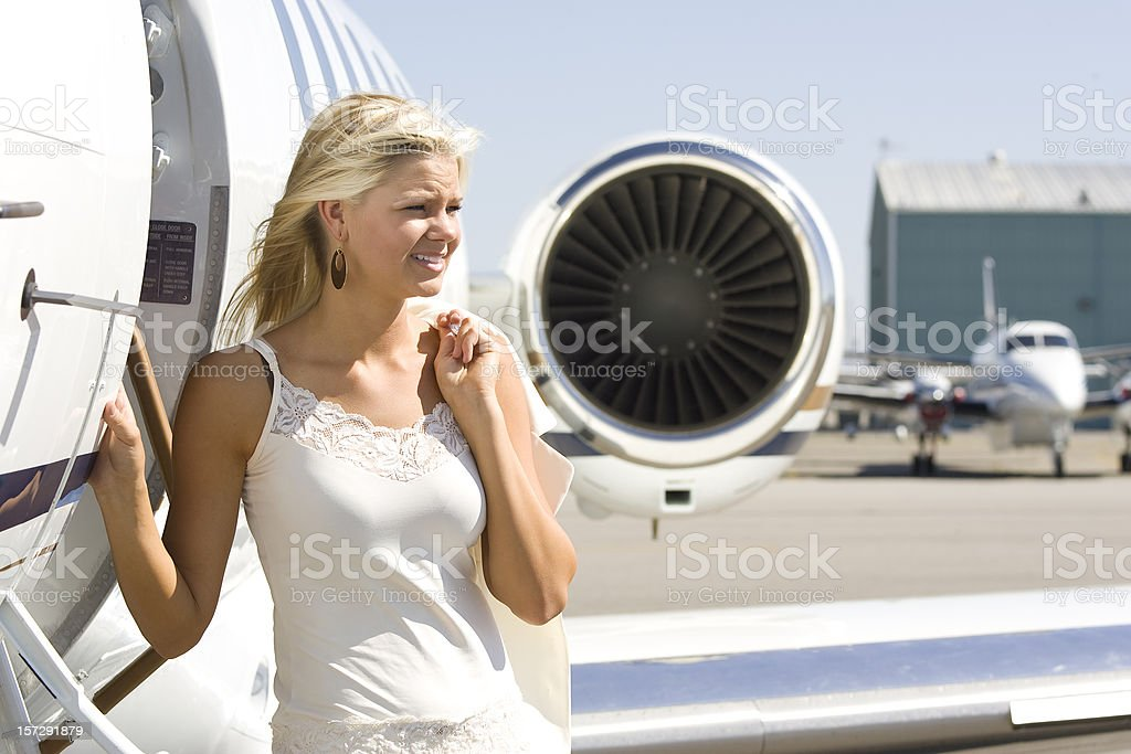 Affluent Travel-Beautiful Blonde Woman by Airplane stock photo