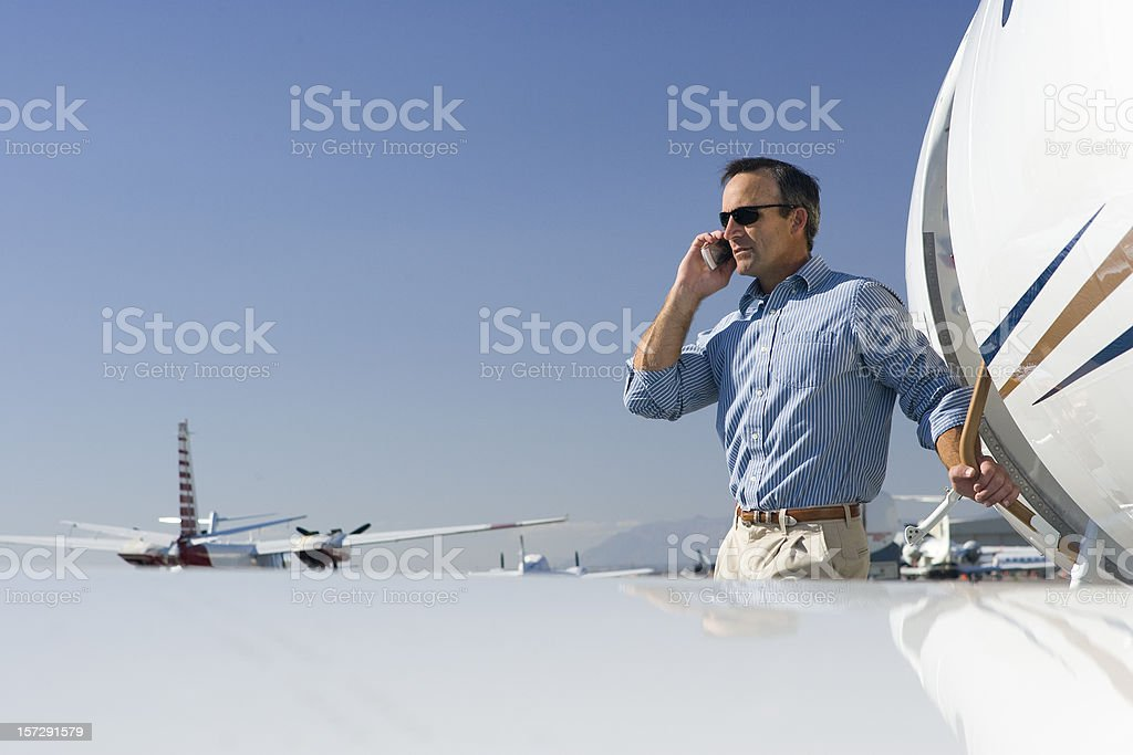 Affluent Travel-Man Talking on Cell Phone by Airplane royalty-free stock photo