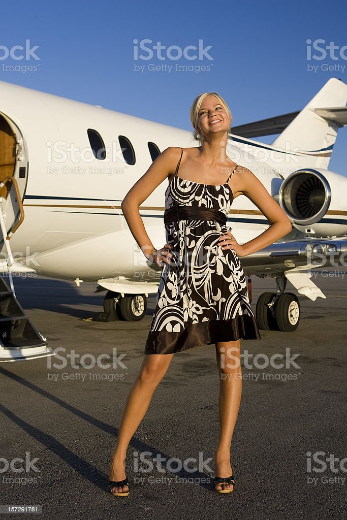 Affluent Travel-Sexy Girl Laughing by Airplane stock photo
