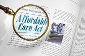 Affordable Care Act with magnifying glass on magazine article +++ inset photo and all text were created by photographer and are copyright free+++
