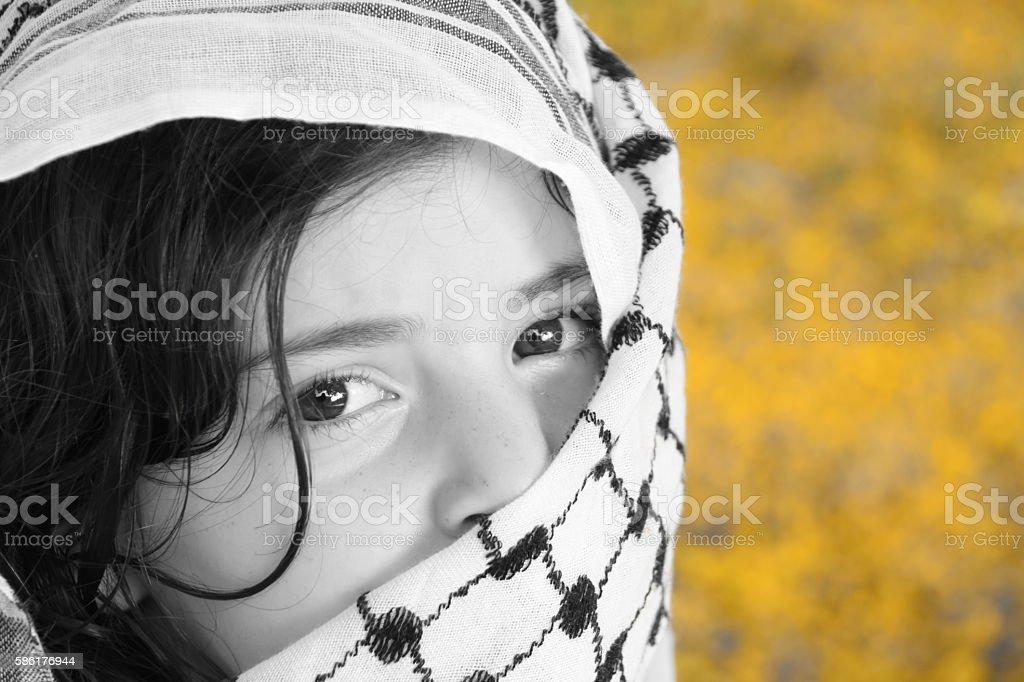 Afghan girl and (Arabic) kaffiyah stock photo