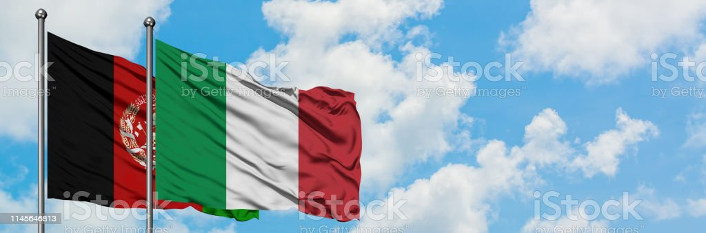 Afghanistan and Italy flag waving in the wind against white cloudy...
