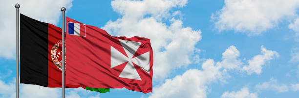Afghanistan and Wallis And Futuna flag waving in the wind against white cloudy blue sky together. Diplomacy concept, international relations. stock photo