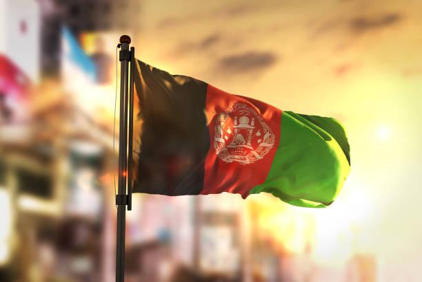 Bandeira do Afeganistão contra cidade turva fundo no Sunrise Backlight - foto de acervo