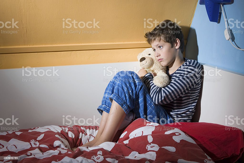 Afraid and depressed young boy A young boy is sitting afraid and depressed on his bed in his bed room Abandoned Stock Photo