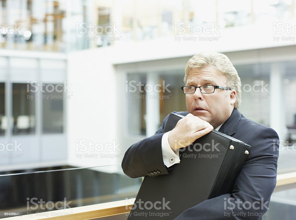 Afraid businessman holding briefcase stock photo