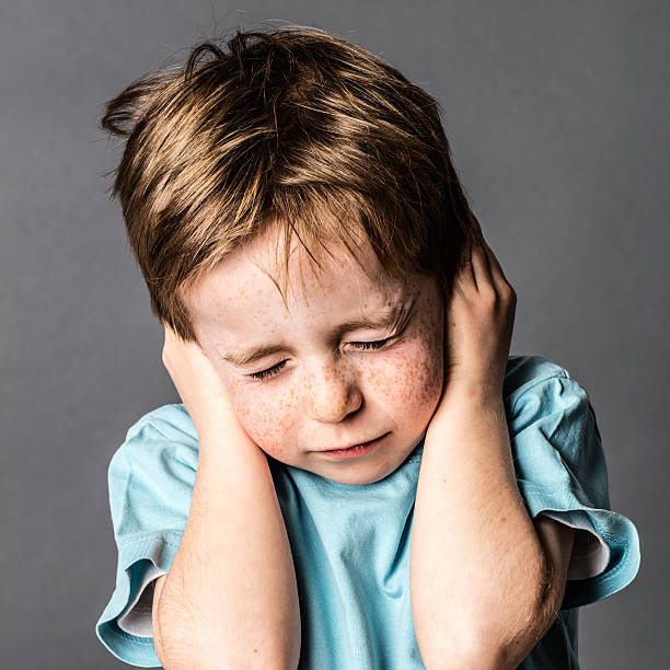 afraid little boy closing ears and eyes against domestic violence frowning little boy closing his ears and eyes against domestic violence or education, afraid of relationship problems, grey background, contrast effects hands covering ears stock pictures, royalty-free photos & images