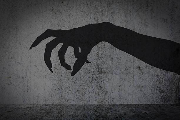 afraid of a big monster claw shadow - monstruo fotografías e imágenes de stock