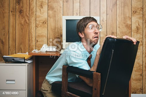 A terrified man and office in 1980's - 1990's style, complete with vintage computer and technology of the time, hides behind his chair at his desk with a look of fear on his face at some crisis or disaster occurring at work.  Wood paneling on the wall in the background.  Horizontal with copy space.