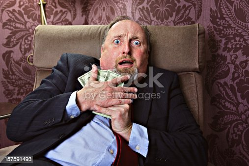Middle aged man hugging US dollars with a frightrened facial expression