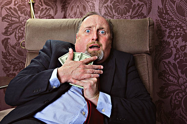 Afraid to loose money Middle aged man hugging US dollars with a frightrened facial expression greed stock pictures, royalty-free photos & images