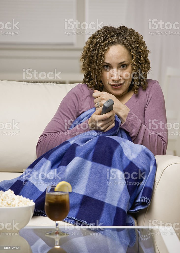 Afraid woman under blanket with remote control watching television stock photo