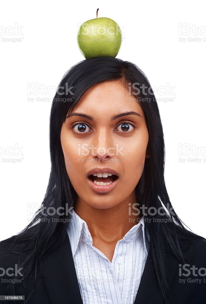 Afraid young businesswoman with green apple on head royalty-free stock photo
