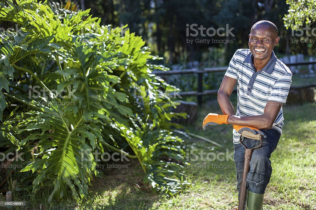 African adult male taking a break from gardening stock photo