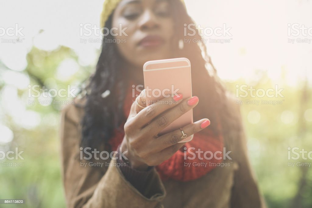 African America girl in park using smart phone. Focus  is on hand. royalty-free stock photo