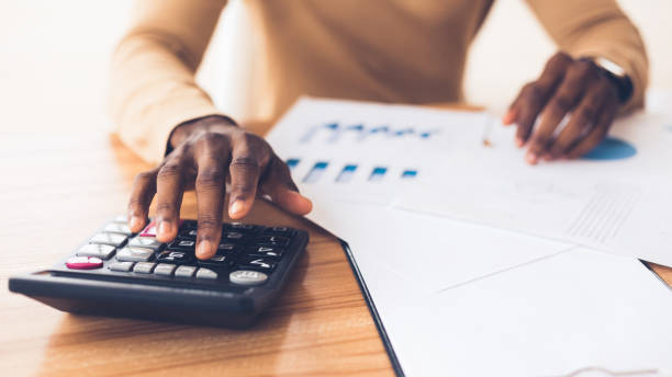 African american accountant calculating budget of the company Budget Planning. Unrecognizable black businessman using calculator, tracking income and expenses. Panorama, copy space calculator stock pictures, royalty-free photos & images