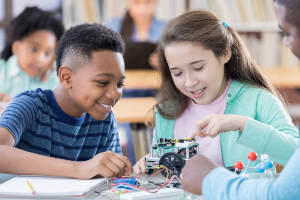 African American and Hispanic students build a robot together stock photo