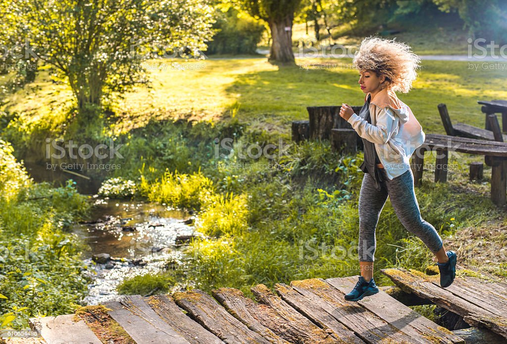 African American athlete running over the bridge in nature. – Foto