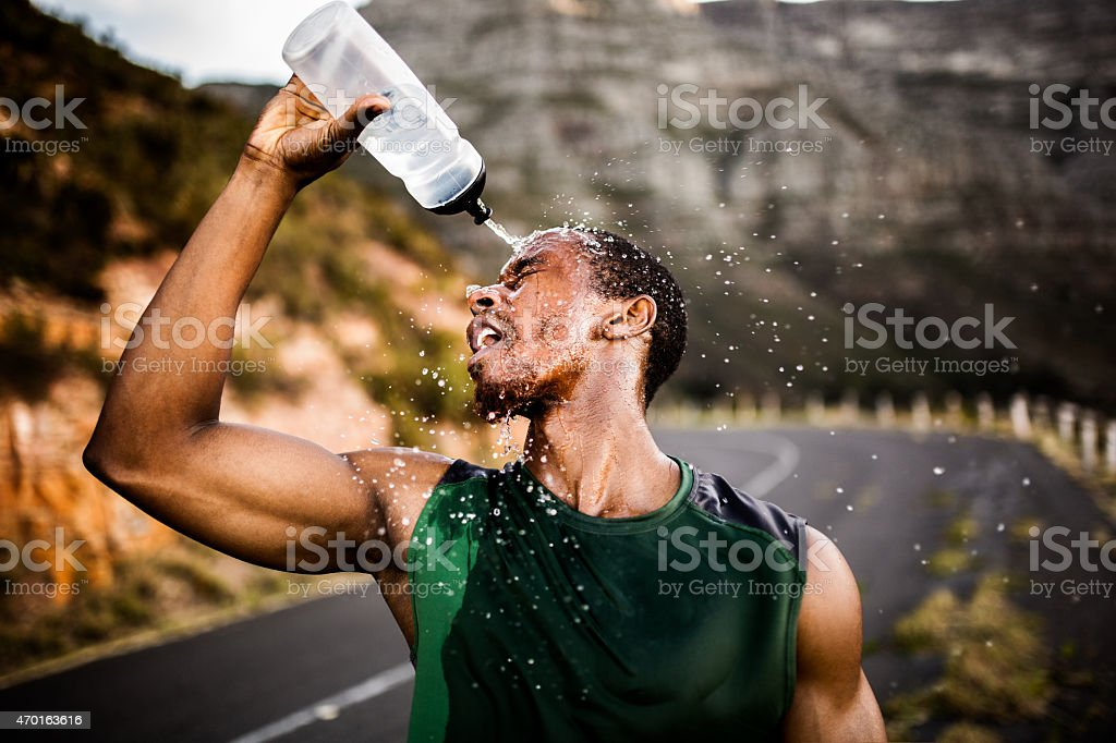 African American athlete splashing water on his face after excer stock photo