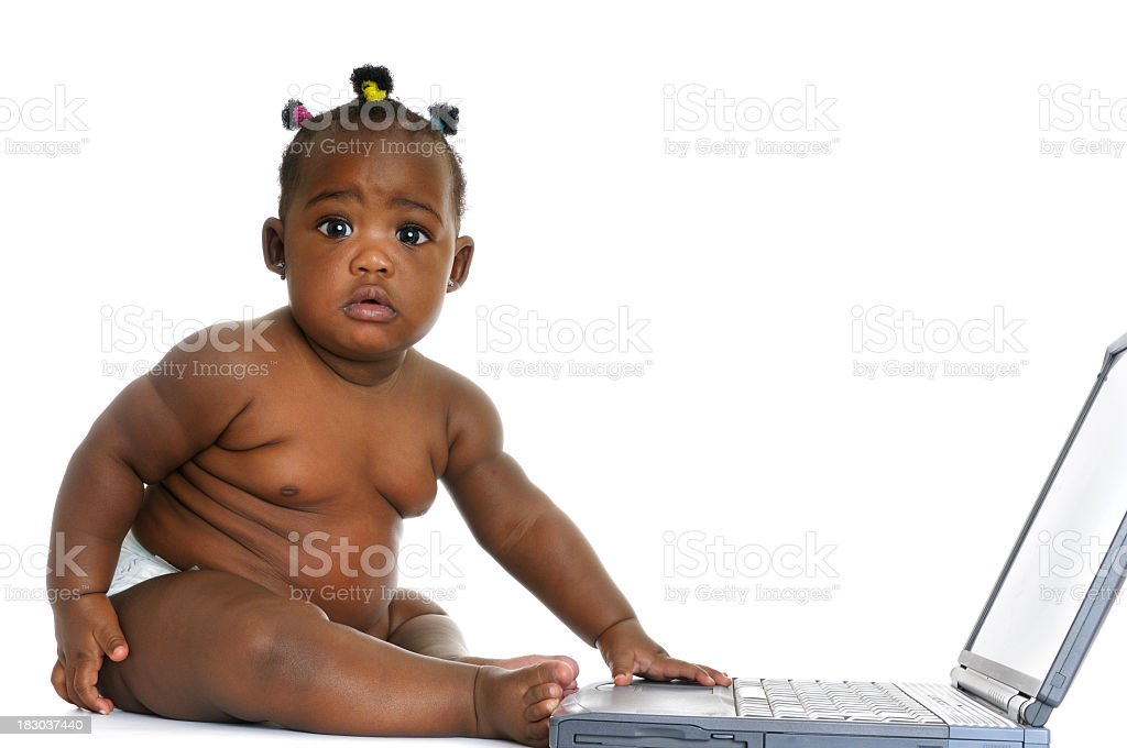 African American Baby Girl Sitting In Front Of A Laptop stock photo