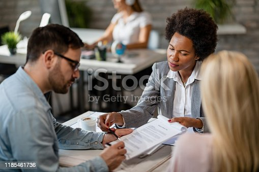 944314580 istock photo African American bank manager and a couple signing a contract in the office. 1185461736