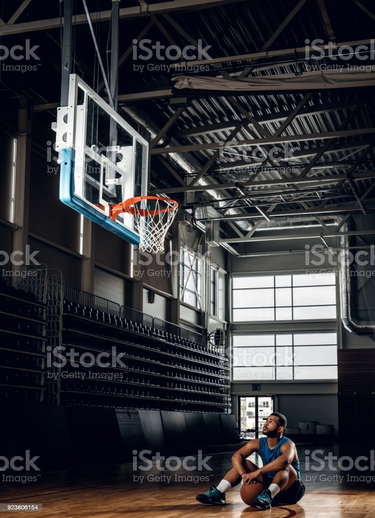 Portrait of African American basketball player sits on a floor under...