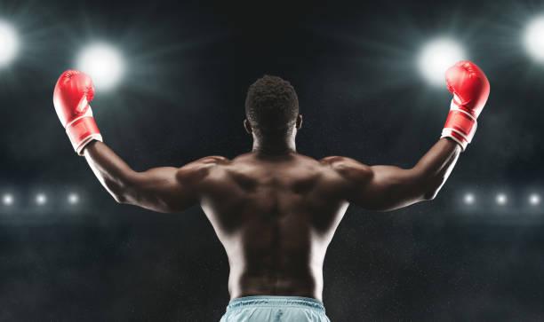 african american boxer raising his arms in winner gesture - indumento sportivo protettivo foto e immagini stock