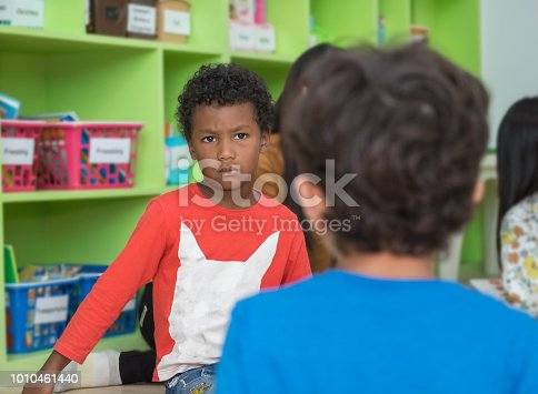 istock African american boy angry and looking at friend in school library in kindergarten.kids education concept. 1010461440