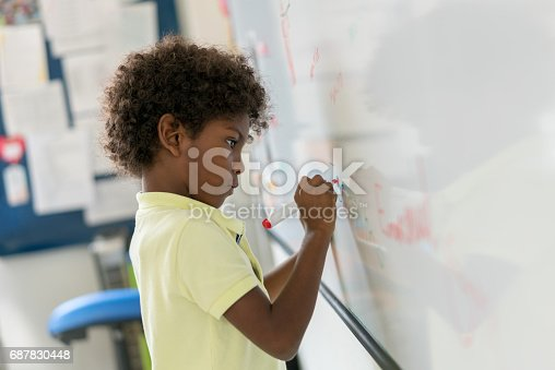 istock African American boy at the school writing on the board 687830448
