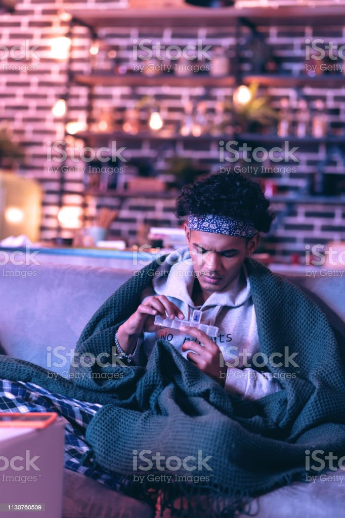 African American boy checking how many pills he left to taking. Health responsibility. Serious African American boy checking pills case to consider how many pills he left to taking. Adult Stock Photo