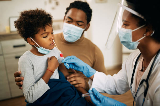 African American boy having PCR test at doctor's office during coronavirus pandemic. stock photo