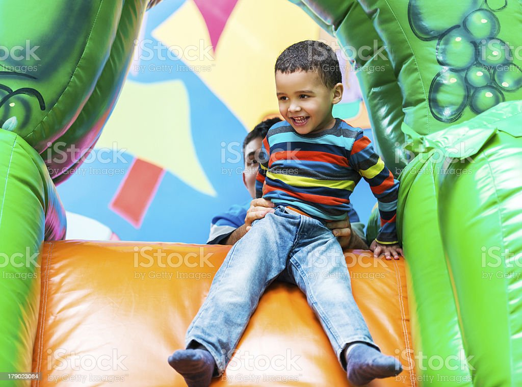 African American boy on an inflatable slide. royalty-free stock photo