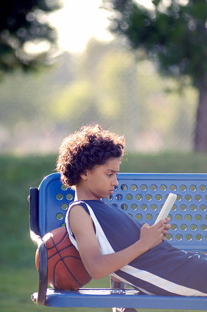 African American Boy reading a mobile tablet in the park stock photo
